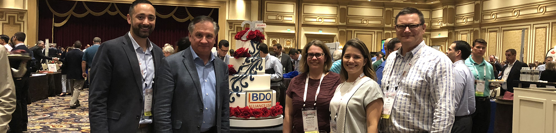 group of staff standing with 'bdo' bags in conference hall
